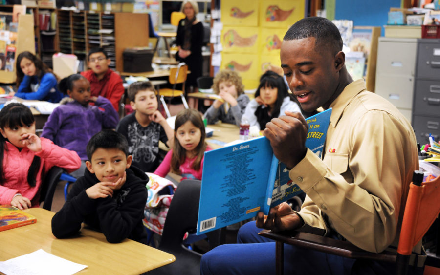 A man reads a Dr. Seuss book to a classroom of children.
