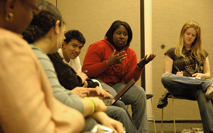 A student gestures and speaks while other students watch.